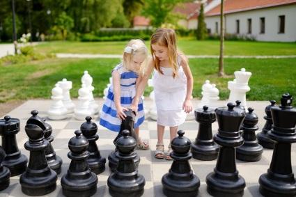 Deux filles qui jouent aux échecs sur un échiquier géant